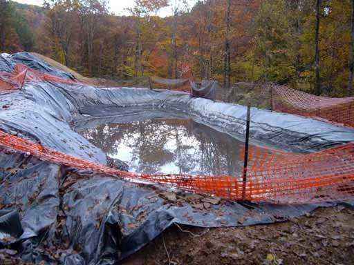 "Figure 9. Drilling pit. After it is full of cuttings and chemicals it is folded over (""toxic burrito"") and either buried or hauled off"